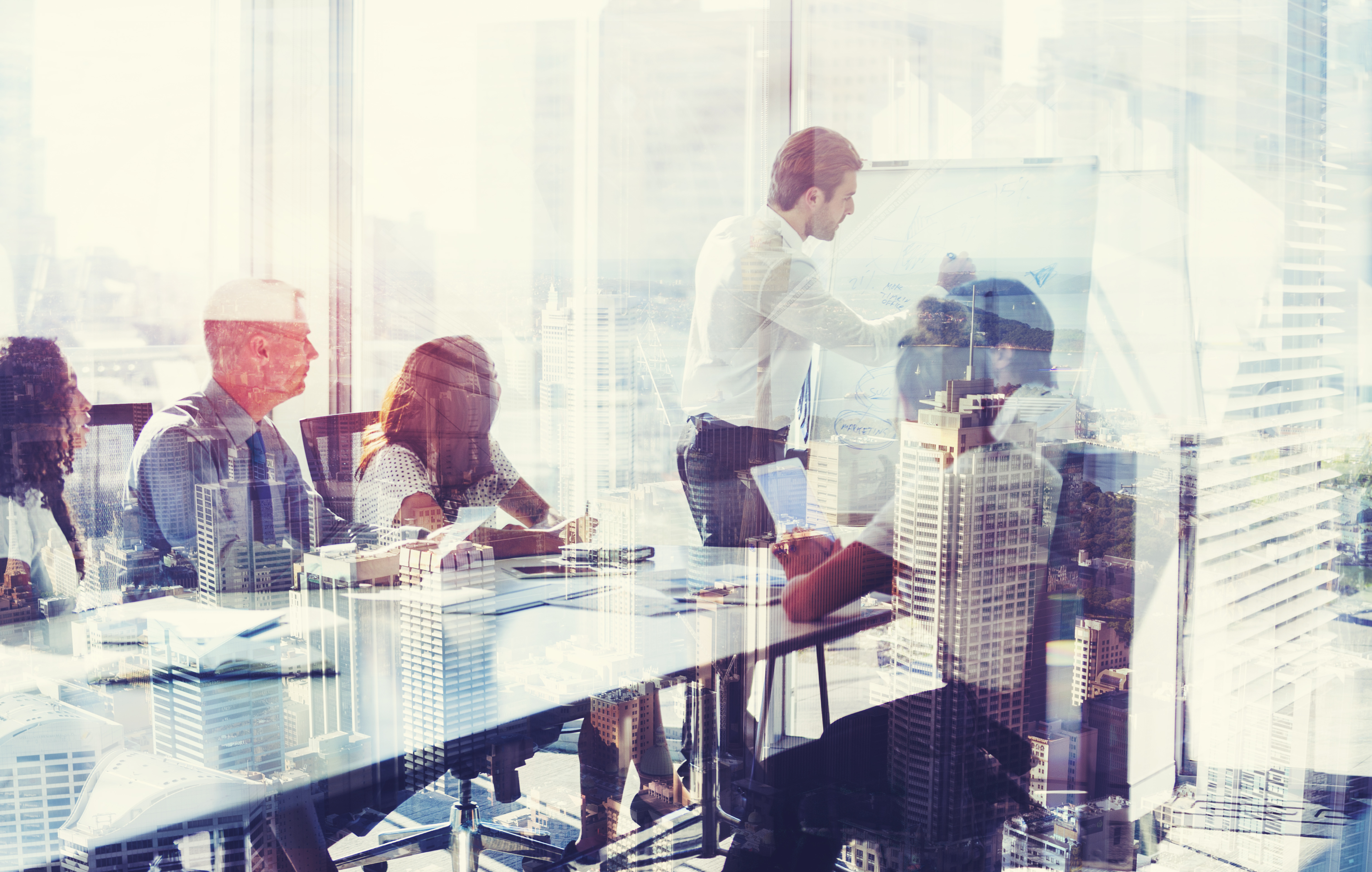Montage of a team of business people at a presentation at the boardroom table. There are several buildings in an overlaid cityscape. There is also motion blurred traffic on a roadway in the middle of the group. City is Sydney, Australia. Business development; growth and architecture